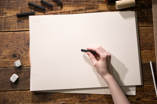 Close-up view of a painter on a white sheet. A man holds a pencil and draws. Drawing and creativity concept.