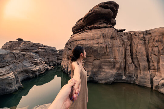 Asian woman holding hands with couple in rock gorge of grand canyon at evening