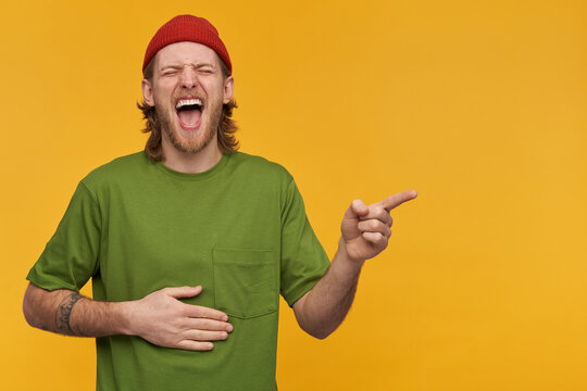 Guy with blond hair and beard. Wearing green t-shirt and red beanie. Touching belly and laughing hard with closed eyes. Pointing finger to the right at copy space, isolated over yellow background