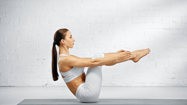 Side view of brunette woman sitting in boat pose on yoga mat.