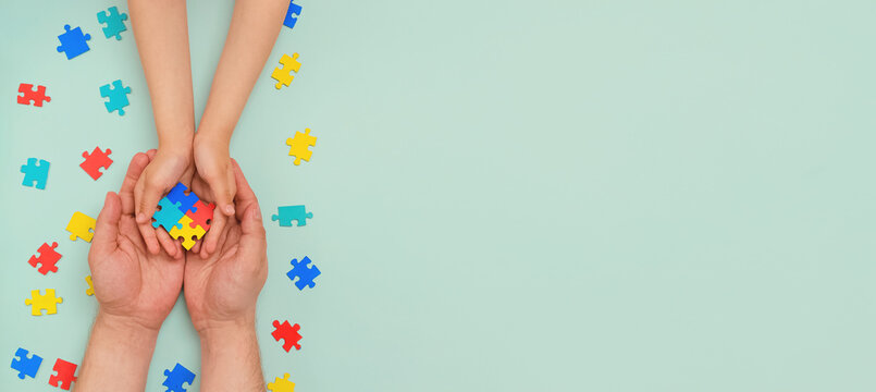 World autism awareness day. Understanding - love concept. The hands of an autistic father and child hold a colorful puzzle on blue background. ASD. Heart of puzzles.Copy space. Banner. Layout
