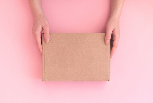 Delivery woman hold parcel box with copy space on pink background, mockup or template of cardboard box