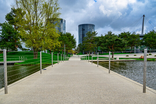 Beautiful footbridge over a calm lake in the green Autostadt park in Wolfsburg, Germany