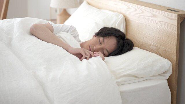 ベッドで安眠する男性