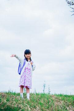 ランドセルを背負って手を振る小さな女の子