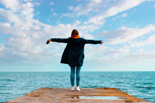A woman in a jacket stands on the edge of the dock, her arms outstretched in flight. In the background, the blue sea and the sky with clouds. Copy space. The concept of freedom and inspiration