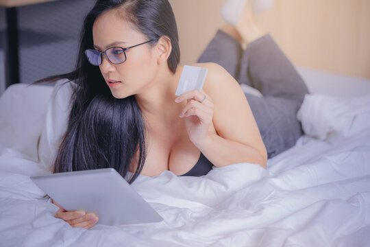Young sexy woman on the bed entering credit card number on smart pad shopping online at home.