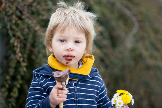 Cute blond child, boy, eating ice cream in the park