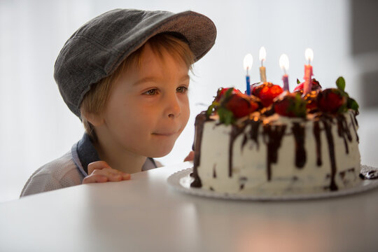 Four years old blond child, preschool boy, celebrating birthday at home with homemade cake