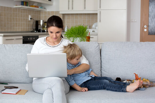 Mother, working on her laptop and taking phone calls, child playing next to her at home