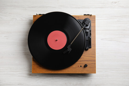 Modern vinyl record player with disc on white wooden background, top view