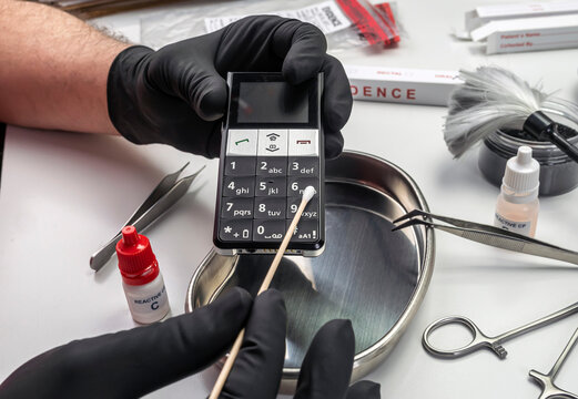 Police scientist takes DNA samples from phone involved in murder in lab, conceptual image