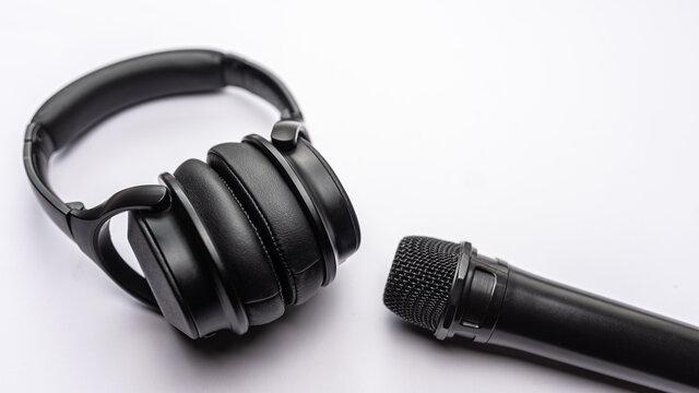 Kopfhörer und Mikrofon liegen auf weißem Hintergrund