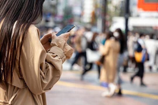 渋谷でスマホを操作する若い女性の手元