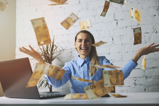 successful cheerful business woman throwing euro banknotes in office. falling money