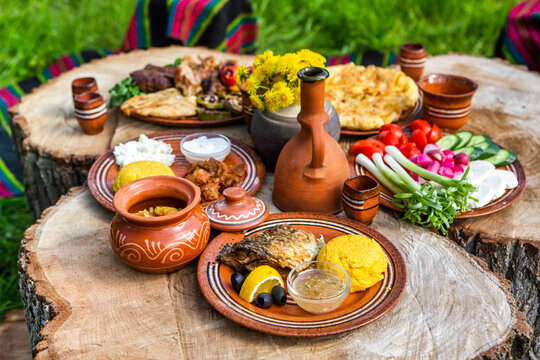 Homemade Romanian Food with grilled meat, polenta and vegetables Platter on camping. Romantic traditional Moldavian food outside on the wood table.