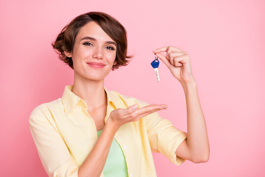 Photo of pretty charming young lady dressed yellow shirt holding new apartment keys isolated pink color background