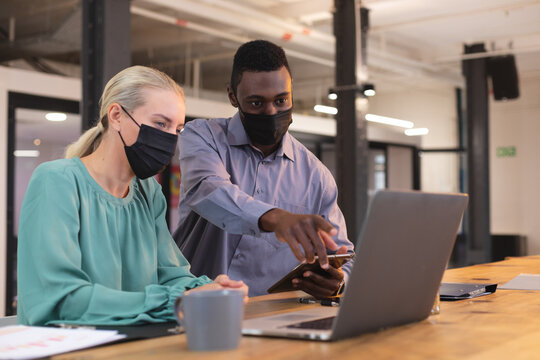 Diverse male and female office colleagues wearing face masks discussing over laptop at modern office