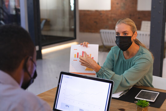 Caucasian male and female office colleagues wearing face masks discussing over a document at office