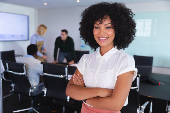 Portrait of african american woman smiling while standing in the meeting room at modern office