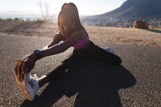 Fit african american woman stretching on ground, exercising in countryside