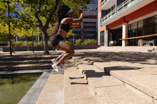 Fit african american woman jumping on steps exercising in city