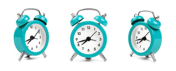 Three teal blue alarm clock over white