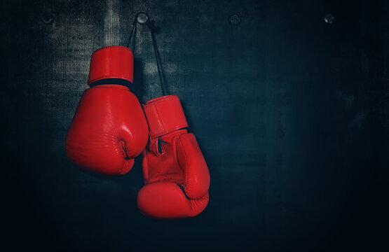 Red leather boxing gloves hanging on black wall