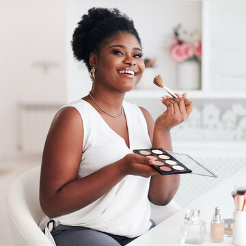 Beautiful African American Woman applying her makeup on with professional cosmetics products at home