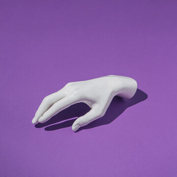Plastic human hand on purple background. Minimal creative futuristic concept.