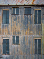 Windows and the corrugated iron wall of an abandoned factory
