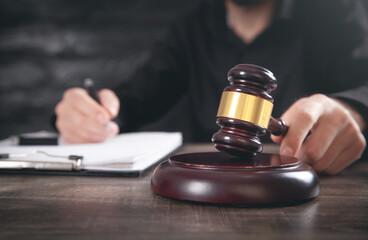 Male judge in a courtroom striking the gavel. - fototapety na wymiar
