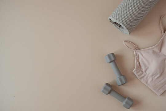 Aesthetic creative flat lay of yoga, fitness, workout training equipment on neutral beige background. Dumbbells, top, mat. Flatlay, top view sport influencer concept