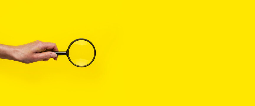 female hand holds a magnifying glass loupe on a yellow background. Banner