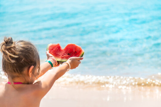 Child girl eats watermelon by the sea. Selective focus.