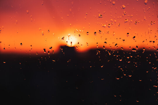 Drops of rain water on the window against the evening sky. Raindrops on the glass, sunset, weather related image