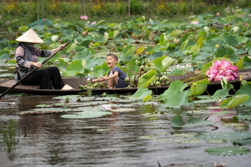 Vietnamese boy playing with mom boating the traditional wooden boat for keep the pink lotus in the big lake at thap muoi, dong thap province, vietnam, culture and life concept