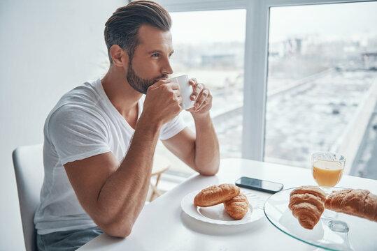 Handsome young man enjoying hot coffee