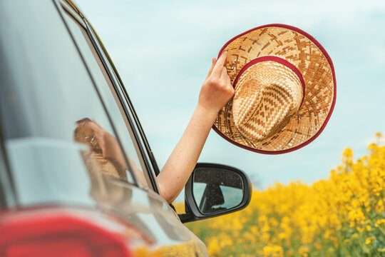 Woman enjoying car ride in summer countryside landscape, hand with straw hat reaching out the window