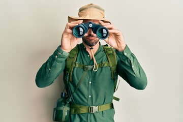 Obraz Handsome man with beard wearing explorer hat looking through binoculars skeptic and nervous, frowning upset because of problem. negative person. - fototapety do salonu
