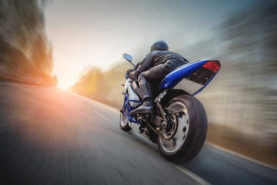 A motorbiker is rushing along the empty road at the high speed concept. Freedom.