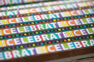 Fototapeta scrapbooking paper with the word celebrate repeated multiple times on multicoloured squares and black with dots - macro lens (shallow depth of field) obraz