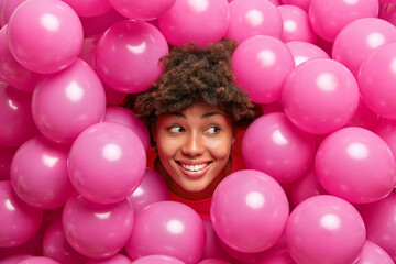Happy cute young African American woman with curly bushy hair smiles broadly looks right has festive mood poses around inflated helium pink balloons expresses positive emotions. Holiday decor.