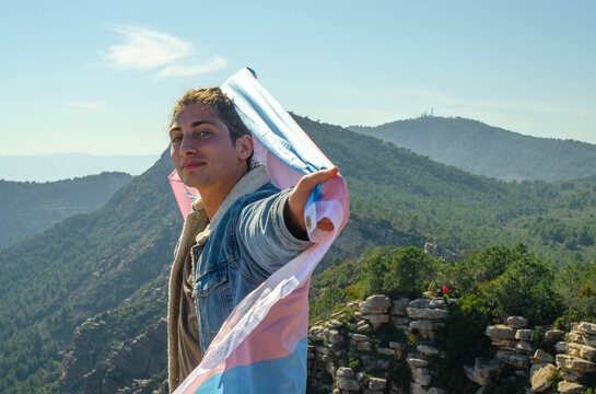 Clear Eyed Young Man Looking at Camera Defiantly while Holding Blue and Pink LGBT Trans Flag in Denim Jacket with Mountain Cliff Background
