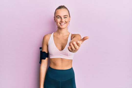 Beautiful blonde woman wearing sportswear and arm band smiling friendly offering handshake as greeting and welcoming. successful business.
