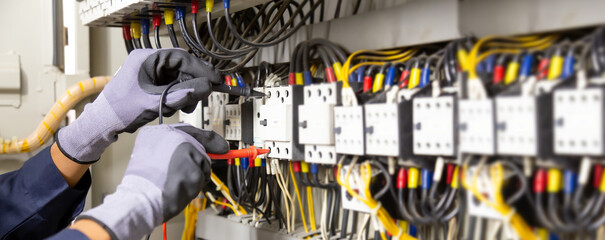 Electrician engineer tests electrical installations and wires on relay protection system....