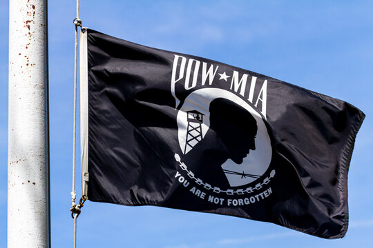 Annapolis, MD,USA 05-02-2021: POW, MIA (Prisoner of War, Missed in Action) Flag flying in  wind on a sunny day. Emblem depicts silhouette of a prisoner with barbed wire and guard tower in background