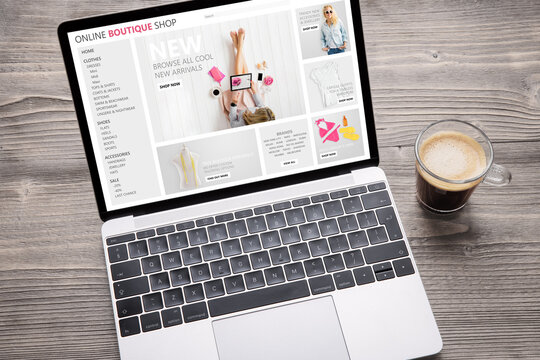 Laptop with website of online fashion store on screen