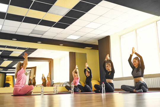 Attractive female coach lead yoga class teach Caucasian group of people meditating together, girls raised arms up make Namaste gesture seated in lotus pose working out indoor