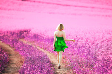 Wall Murals Candy pink girl in a field of lilac flowers in lavender colors, violet and pink landscape, happy and harmony